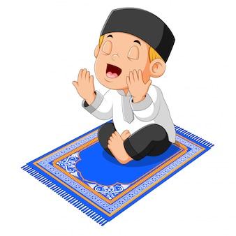Il ragazzo sta pregando e seduto sul tappeto blu della preghiera