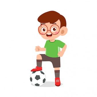 Il ragazzo sveglio del bambino gioca a calcio come attaccante