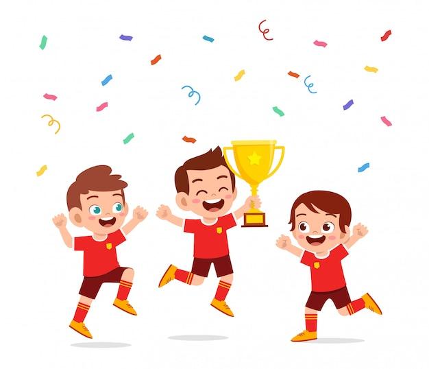 Il ragazzo sveglio felice dei bambini vince il calcio