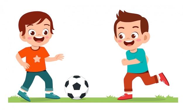 Il ragazzo sveglio felice del bambino gioca a calcio