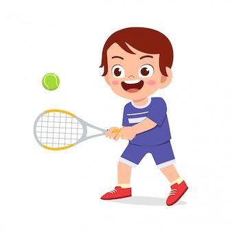 Il ragazzo sveglio felice del bambino gioca a tennis del treno