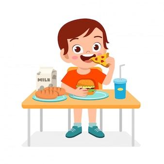 Il ragazzo sveglio felice del bambino mangia gli alimenti a rapida preparazione