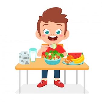 Il ragazzo sveglio felice del bambino mangia l'alimento sano