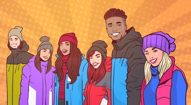 Il ritratto del gruppo di persone sorridente indossa i vestiti dell'inverno sopra i giovani adulti della retro della miscela del fondo di stile variopinto della corsa