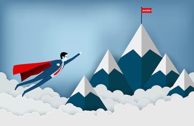 Il supereroe sta volando verso l'obiettivo della bandiera rossa sulle montagne mentre vola sopra una nuvola