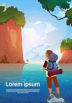 Il viaggiatore con zaino e sacco a pelo dell'uomo gode della vista in viaggiatore del lago mountains sul concetto di vacanza di avventura dell'estate