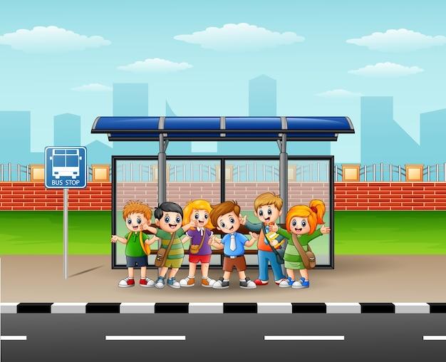 Illustrazione di bambini felici in una fermata dell'autobus