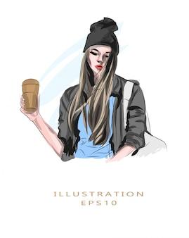 Illustrazione. giovane donna in una giacca e cappello con i capelli volanti. la bella donna sta bevendo il caffè. lo studente. goditi il gusto e l'odore del caffè caldo fresco.