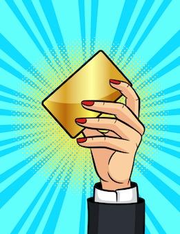 Illustrazione in stile pop art, mano femminile in possesso di una carta di plastica dorata
