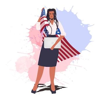 Imprenditrice con bandiera usa tenendo la festa del lavoro del computer portatile