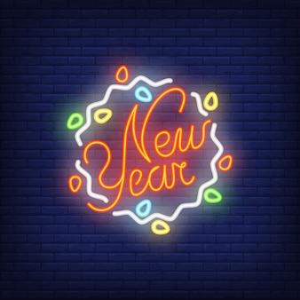 Insegna al neon del nuovo anno con la ghirlanda. Concetto di Natale per la pubblicità luminosa di notte.