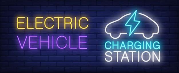 Insegna al neon della stazione di carico del veicolo elettrico. sagoma di auto e fulmini sul muro di mattoni