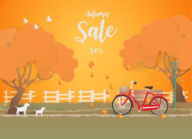 Insegna di vendita di autunno con la bicicletta rossa sotto l'albero