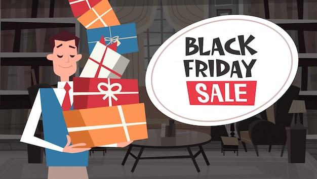 Insegna di vendita di black friday con l'uomo che tiene acquisto dei regali di festa di molti contenitori di regalo