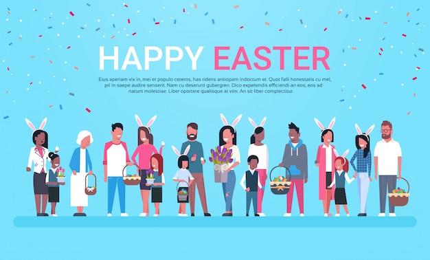 Insegna felice della cartolina d'auguri di pasqua con il gruppo di persone che celebrano le orecchie di coniglietto di usura di festa e canestri di tenuta