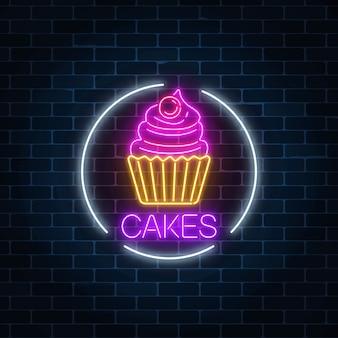 Insegna luminosa al neon della torta con crema e ciliegia nel telaio del cerchio su un muro di mattoni scuro
