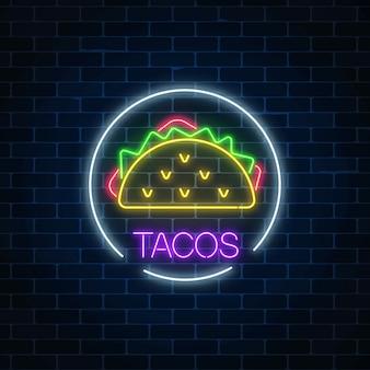 Insegna luminosa al neon di tacos nel telaio del cerchio su un muro di mattoni scuro