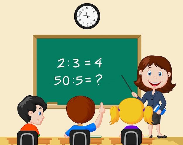 Insegnante che punta alla lavagna e guardando gli scolari in aula
