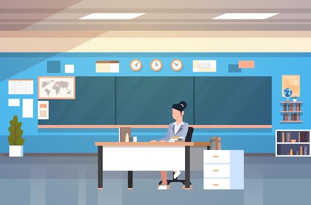 Insegnante della donna dell'interno dell'aula del banco che si siede allo scrittorio sopra il bordo di gesso nella stanza di classe