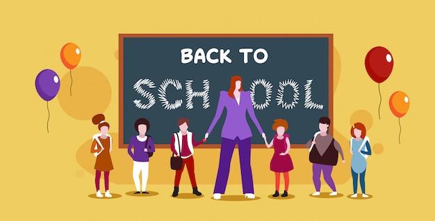 Insegnante felice giorno festa del mondo celebrazione concetto insegnante femminile con scolari che stanno insieme vicino alla lavagna