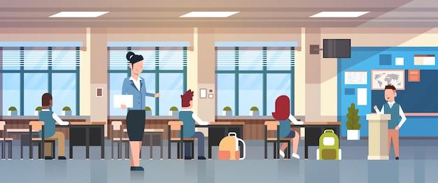 Insegnante femminile with pupils listen to schoolboy con rapporto in piedi a tribune school classroom