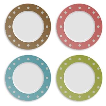 Insieme dei piatti di colore con il modello di pois isolato su bianco