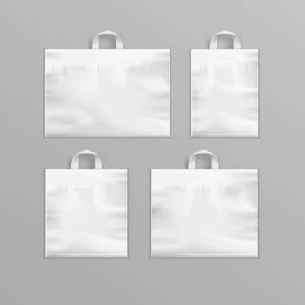 Insieme dei sacchetti della spesa di plastica riutilizzabili vuoti bianchi differenti con le maniglie per la fine di progettazione di pacchetto su isolato su fondo