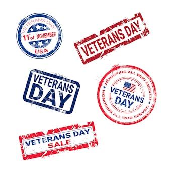 Insieme dei timbri di gomma di lerciume con il distintivo di giorno di veterano su fondo bianco