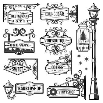 Insieme di etichette d'annata delle lanterne della via con le iscrizioni del palo del metallo sulle insegne e sulle plance di legno