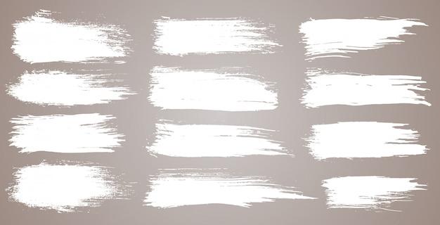 Insieme di pennellate artistiche grunge, pennelli. pennellate larghe dell'acquerello di lerciume. raccolta bianca isolata su fondo bianco