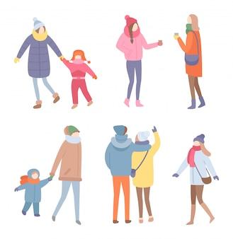 Insieme di persone in piedi nel vettore di vestiti caldi