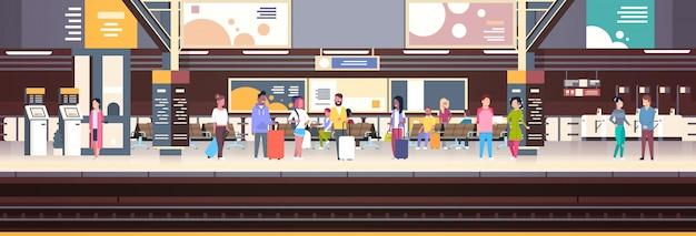 Interno della stazione ferroviaria con i passeggeri che aspettano l'insegna di orizzontale di concetto di trasporto e del trasporto di partenza