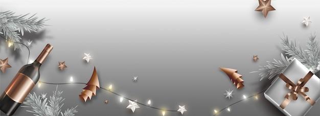 Intestazione o bandiera grigia decorata con il contenitore di regalo, le stelle, la bottiglia di champagne, l'albero di natale della carta di origami e le foglie del pino per la celebrazione di natale.