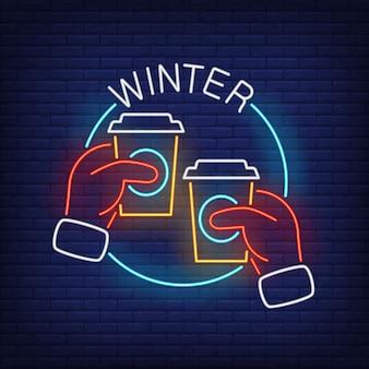 Iscrizione al neon di inverno con le mani in guanti che tengono i bicchieri di plastica