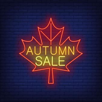 Iscrizione al neon di vendita di autunno sulla foglia di acero rossa
