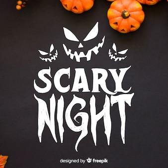 Iscrizione di notte spaventosa con zucche