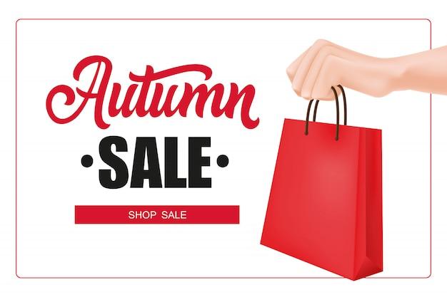 Iscrizione di vendita di autunno nel telaio con la mano che tiene il sacchetto della spesa