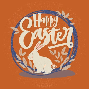 Iscrizione felice di pasqua o desiderio di festa scritto con il carattere corsivo e il coniglietto dentro la struttura o la corona rotonda decorata dalle foglie su fondo arancio. illustrazione disegnata a mano