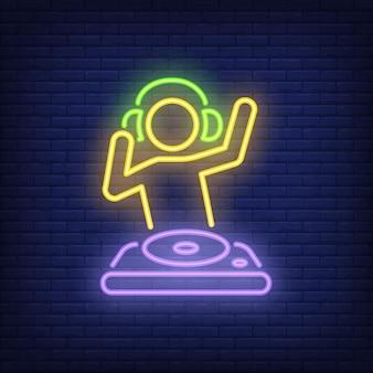 Jokey del disco con l'insegna al neon del miscelatore del dj