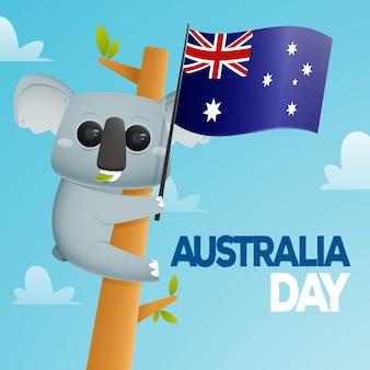 Koala su un tronco che tiene bandiera australiana