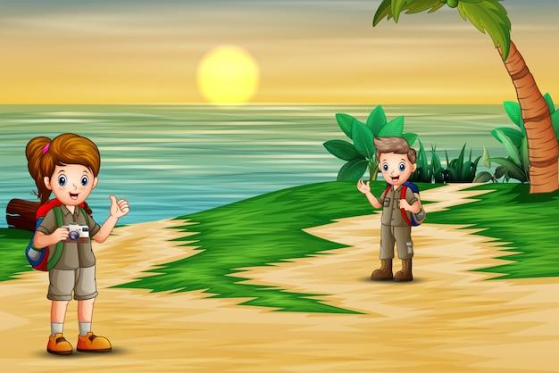 L'esploratore ragazzo e ragazza sulla spiaggia