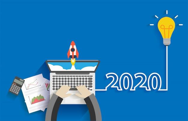 L'idea creativa della lampadina di 2020 nuovi anni di affari inizia con l'uomo d'affari che lavora al computer portatile