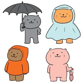L'insieme di vettore del gatto usa l'ombrello e l'impermeabile