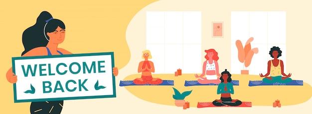 L'istruttrice di yoga mantiene il banner di benvenuto, informando i suoi clienti della ripresa delle lezioni di yoga dopo il blocco covid-19. le donne che fanno padmasana o posa di loto. salute fisica e mentale