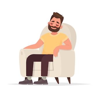 L'uomo barbuto si siede in una poltrona e dorme. una persona riposa o pensa a qualcosa di buono