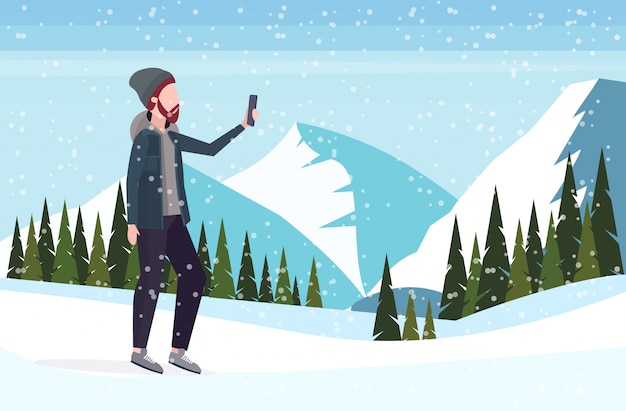 L'uomo che prende la foto del selfie sul personaggio dei cartoni animati maschio casuale della macchina fotografica dello smartphone che posa le montagne nevose abbellisce il fondo integrale