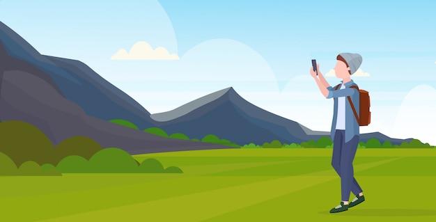 L'uomo che prende la foto del selfie sul personaggio dei cartoni animati maschio casuale della macchina fotografica dello smartphone in cappello con le montagne dello zaino abbellisce l'illustrazione orizzontale integrale del fondo