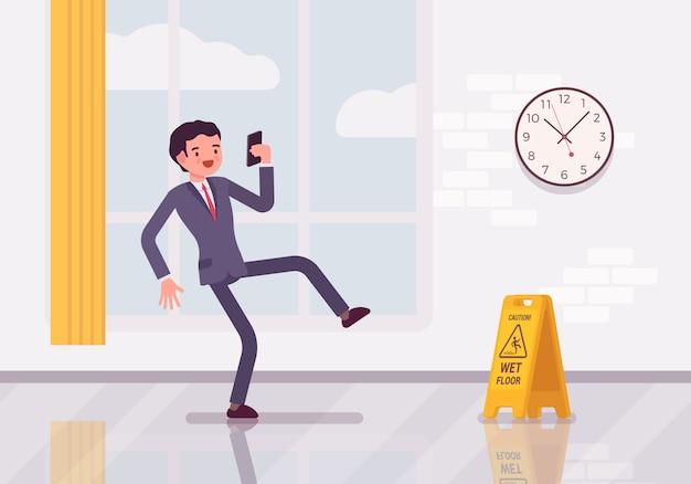 L'uomo con uno smartphone scivola sul pavimento bagnato