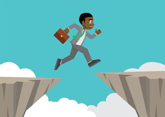 L'uomo d'affari africano salta sopra lo spacco della scogliera.