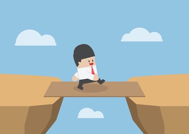 L'uomo d'affari attraversa lo spacco della scogliera dal bordo di legno come ponte